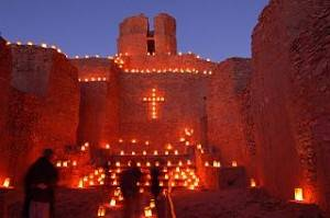 Luminarias and an old mission church in New Mexico by Larry Lamsa