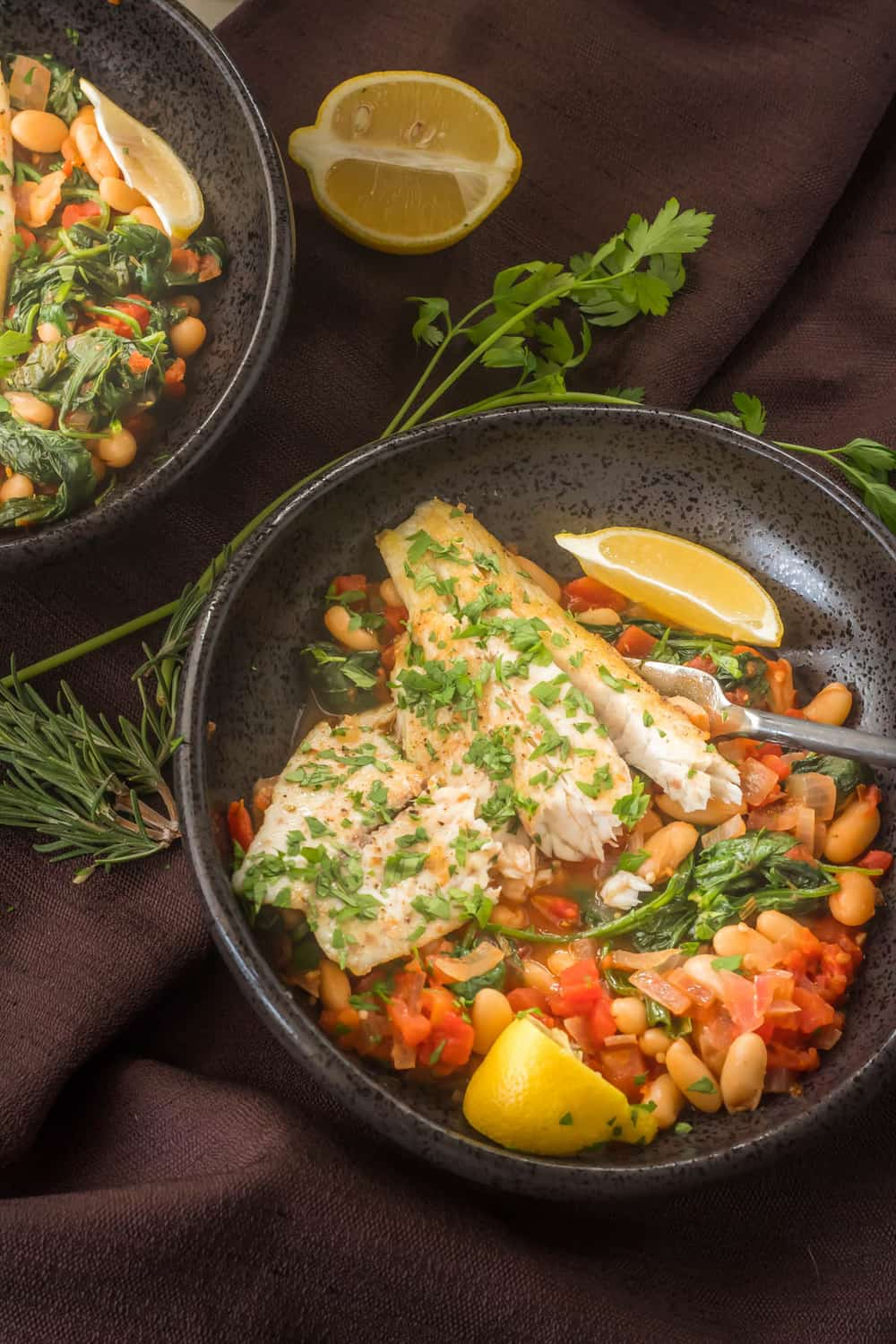 Tuscan Fish With Cannelini Beans, Tomatoes, & Spinach - a close up of the food in a black shallow bowl.