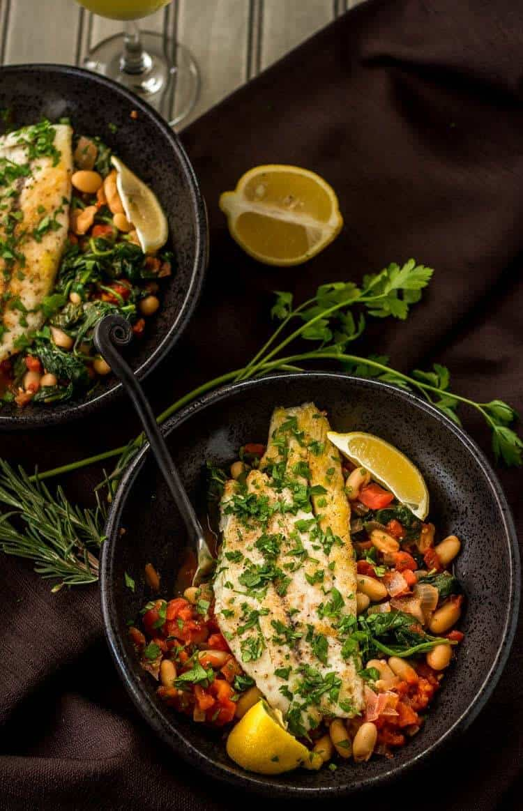 Tuscan Fish With Cannelini Beans, Tomatoes, & Spinach - 2 servings in black ceramic bowls with fresh herbs and lemon
