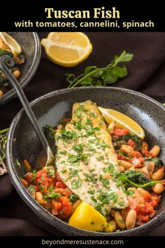 Tuscan Fish with Cannelini Beans, Tomatoes, and Spinach in a black stoneware bowl with fork and lemon wedge.