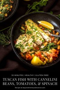 Tuscan Fish with Cannelini Beans, Tomatoes, and Spinach in a black stoneware bowl.