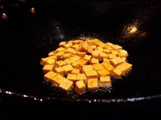 A wok with prepared tofu frying in sesame oil.