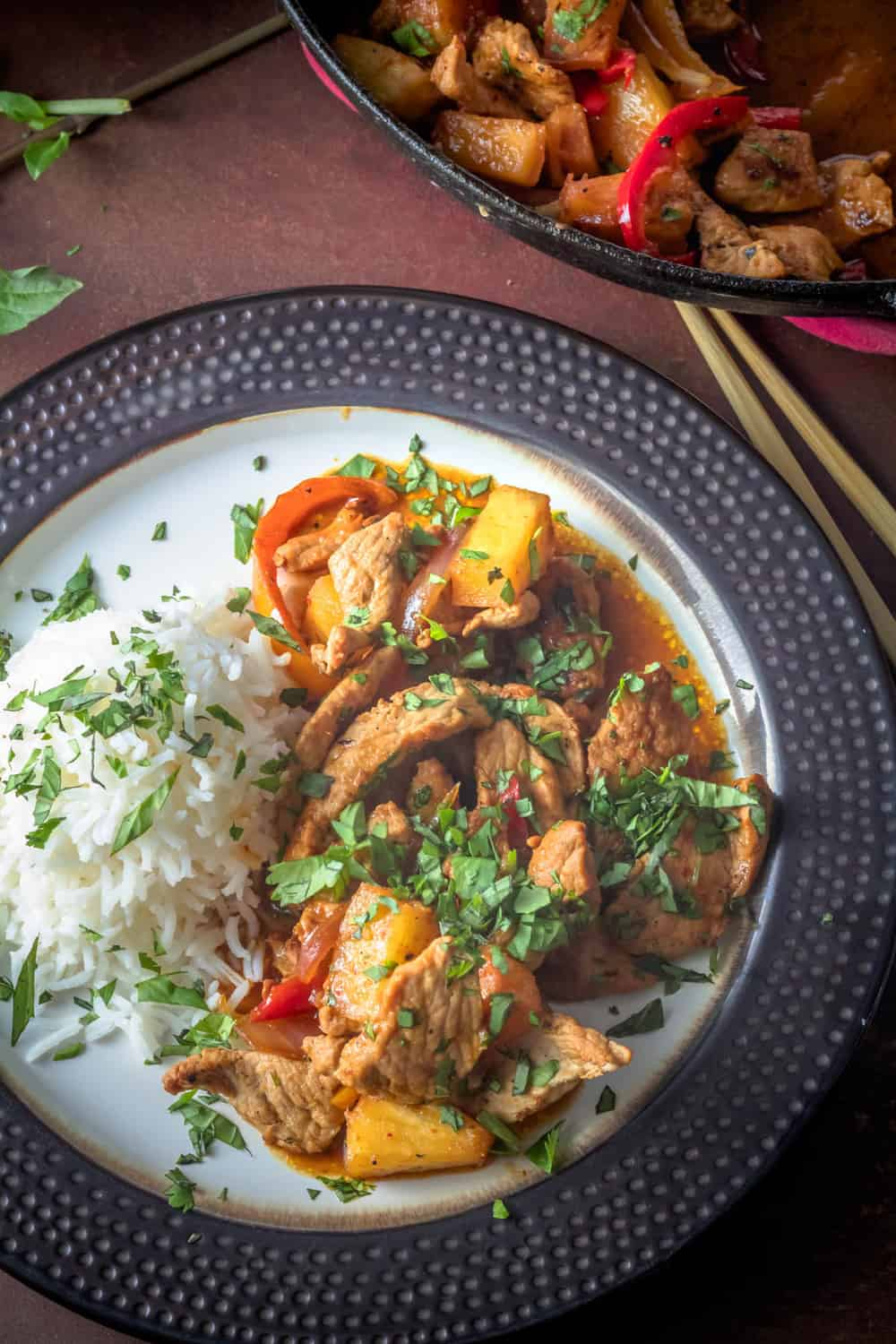 Thai Pork and Pineapple Curry  in a cast iron skillet, a bowl of rice, and a plate of curry and rice garnished with cilantro.