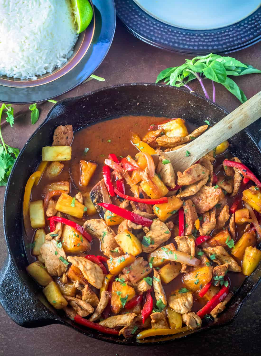 Thai Pork and Pineapple Curry in a skillet with a bowl of jasmine rice and stack of plates.