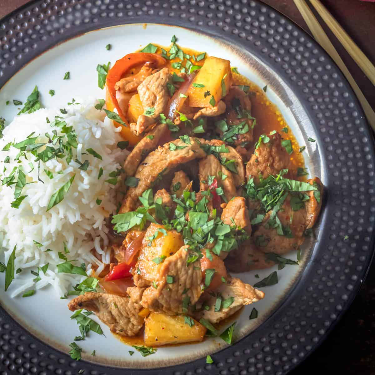 Thai Pork and Pineapple Curry in a bronze rimmed plate with white rice.