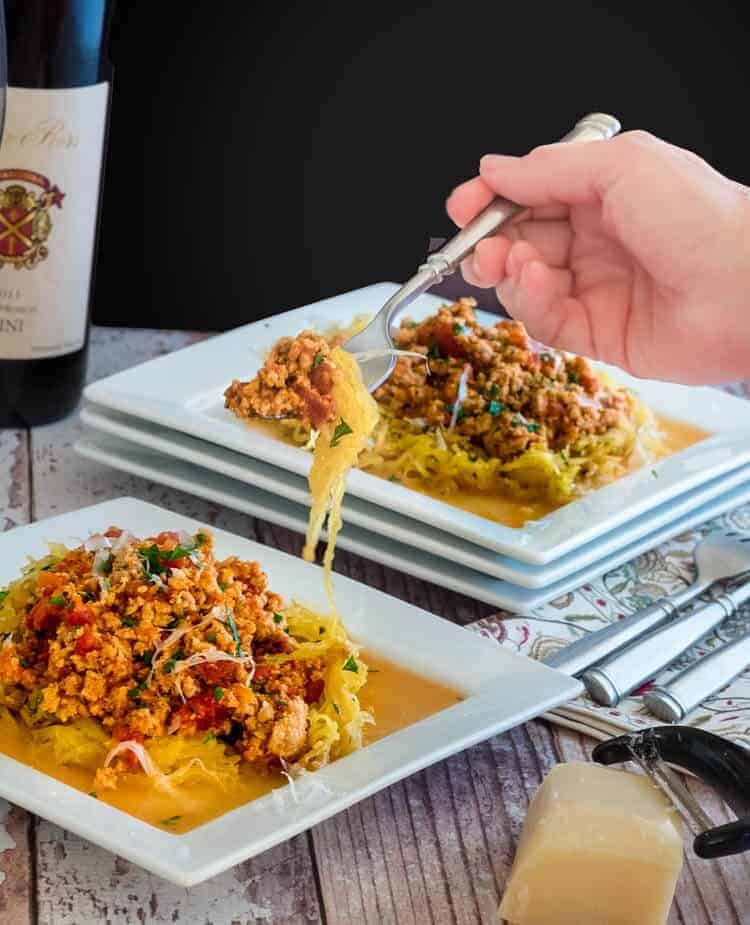 Healthy Turkey Bolognese and Roasted Spaghetti Squash on a fork in hand with a bottle of wine behind.