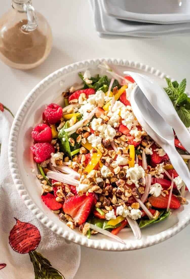 A spinach salad with sliced strawberries, chevre, toasted hazelnuts, sweet bell pepper, shallots with Raspberry Fresh Mint Vinaigrette in a white bowl.