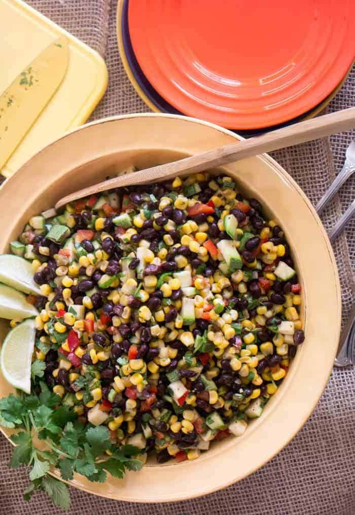Gluten free and vegan Hatch Green Chile, Black Bean and Corn Salad in a yellow ceramic bowl with a wooden spoon