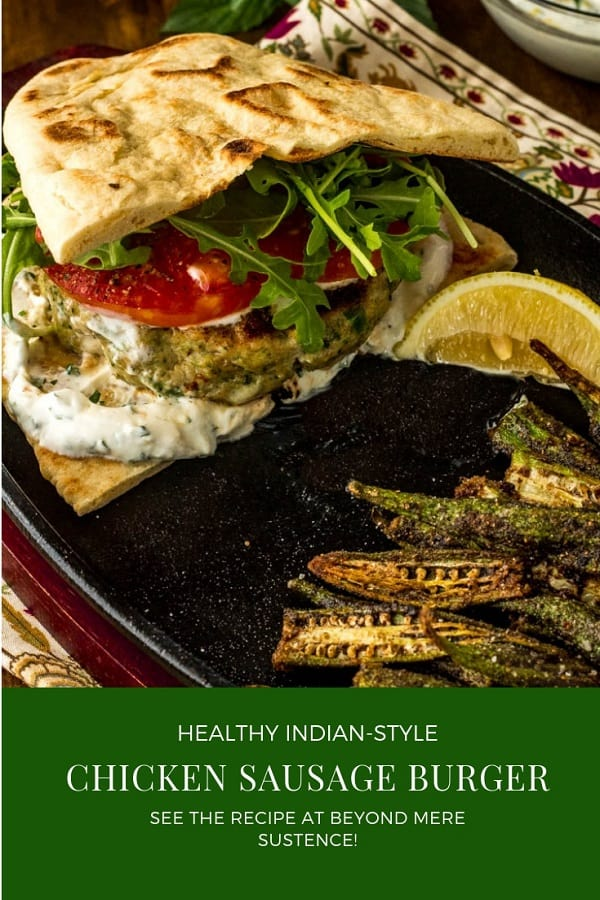Healthy Indian-Style Chicken Burger on a split naan with yogurt sauce, arugula, and tomato.