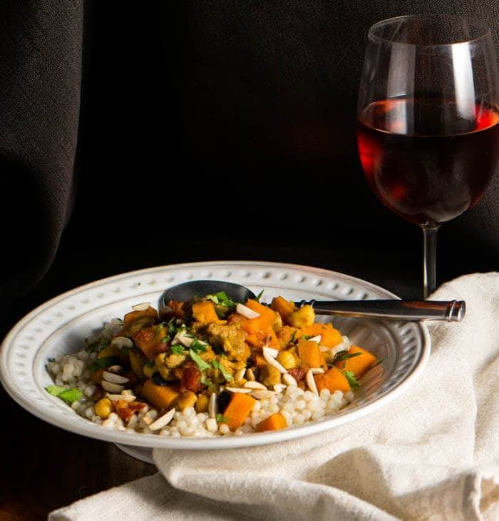 An old 2014 photo of the chicken and vegetable mixture atop Israeli couscous garnished with almonds and mint, a linen napkin, and a glass of rosé.