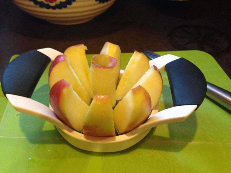 An apple corer/slicer with a honeycrisp apple ready for the spinach salad.