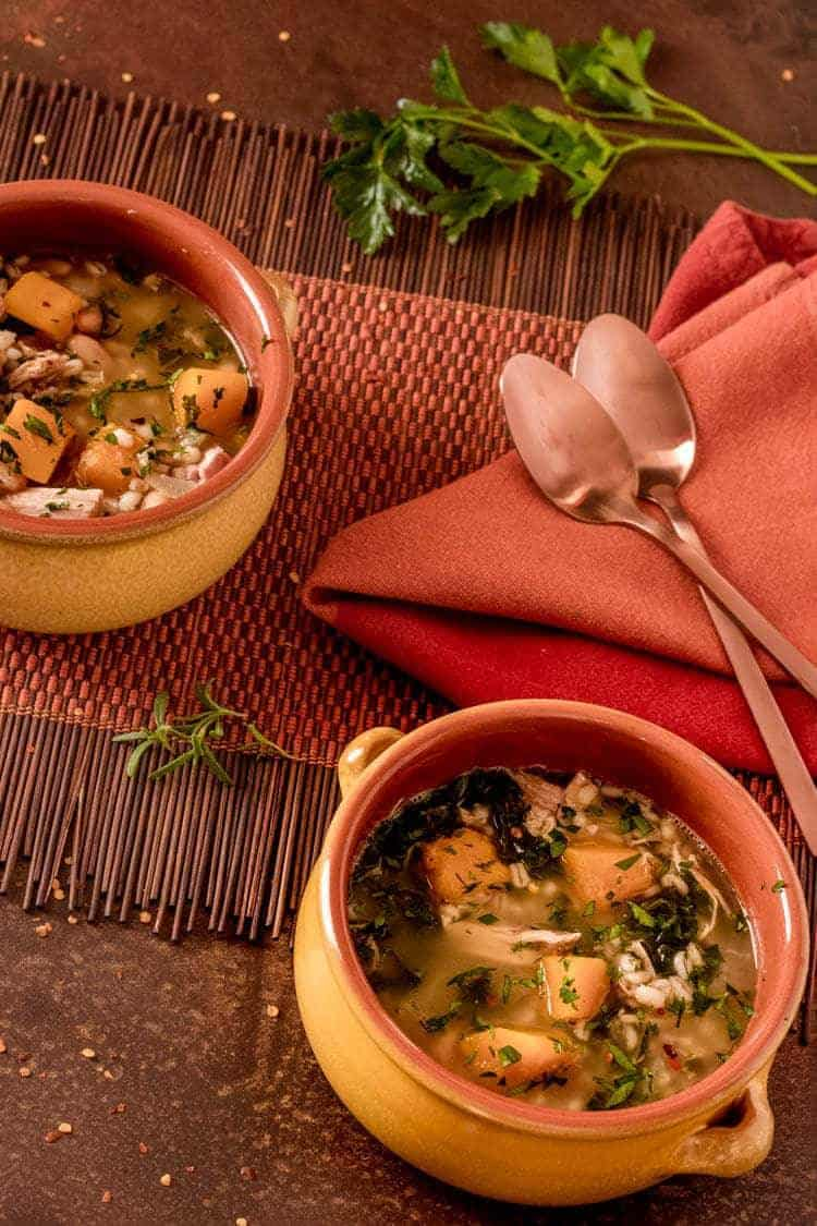 Smoked Turkey and Barley Soup with Kale and Butternut Squash in an earthenware soup bowl.