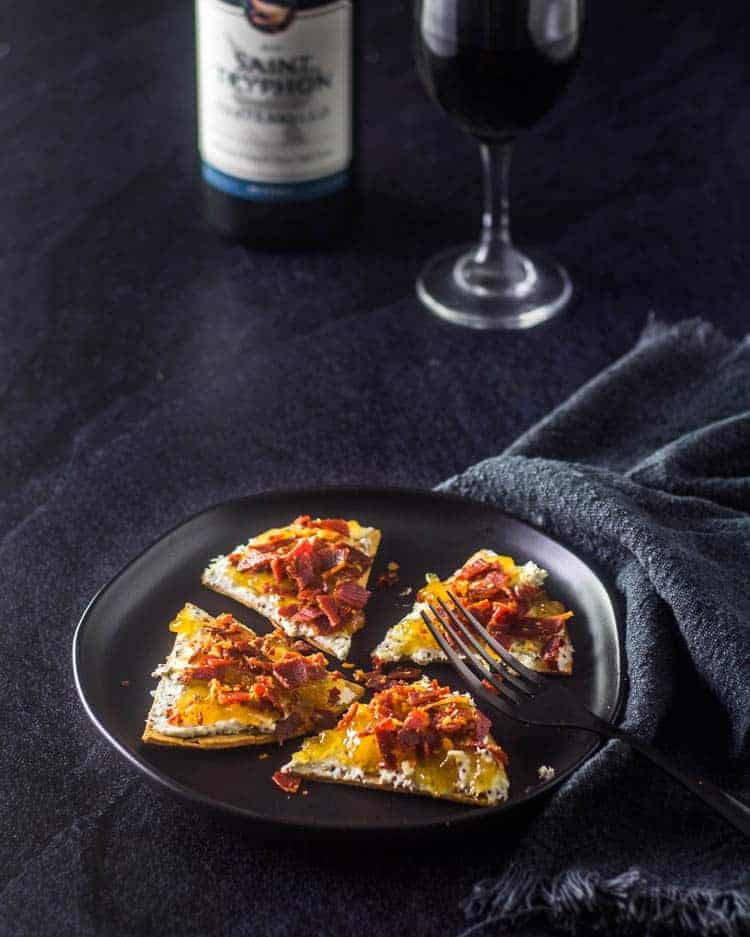 A black stoneware plate and black fork with 4 triangular wedges of Fig Jam and Bleu Cheese Flatbread with Crispy Prosciutto on a black surface with a bottle and glass of red wine in the background.