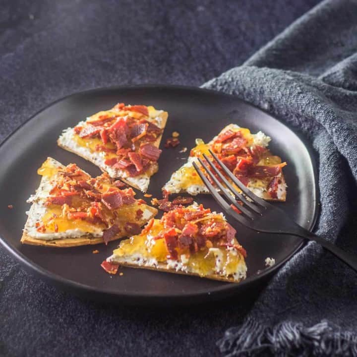 A black stoneware plate with 4 triangular flatbreads spread with bleu cheese, fig preserves, and topped with crispy prosciutto. A black fork and grey napkin complete the image.