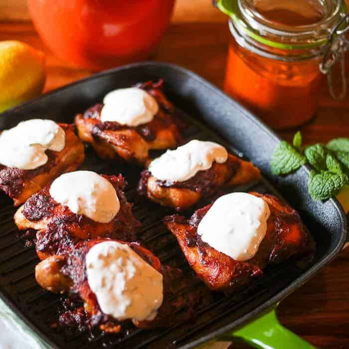 Roasted Harissa Chicken Thighs in a cast iron skillet with yogurt.