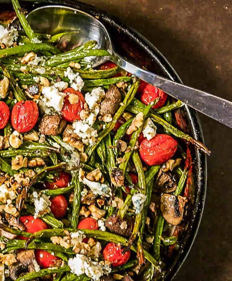 Roasted Green Beans with Tiny Tomatoes and Bleu Cheese in a stoneware roasting pan with spoon.
