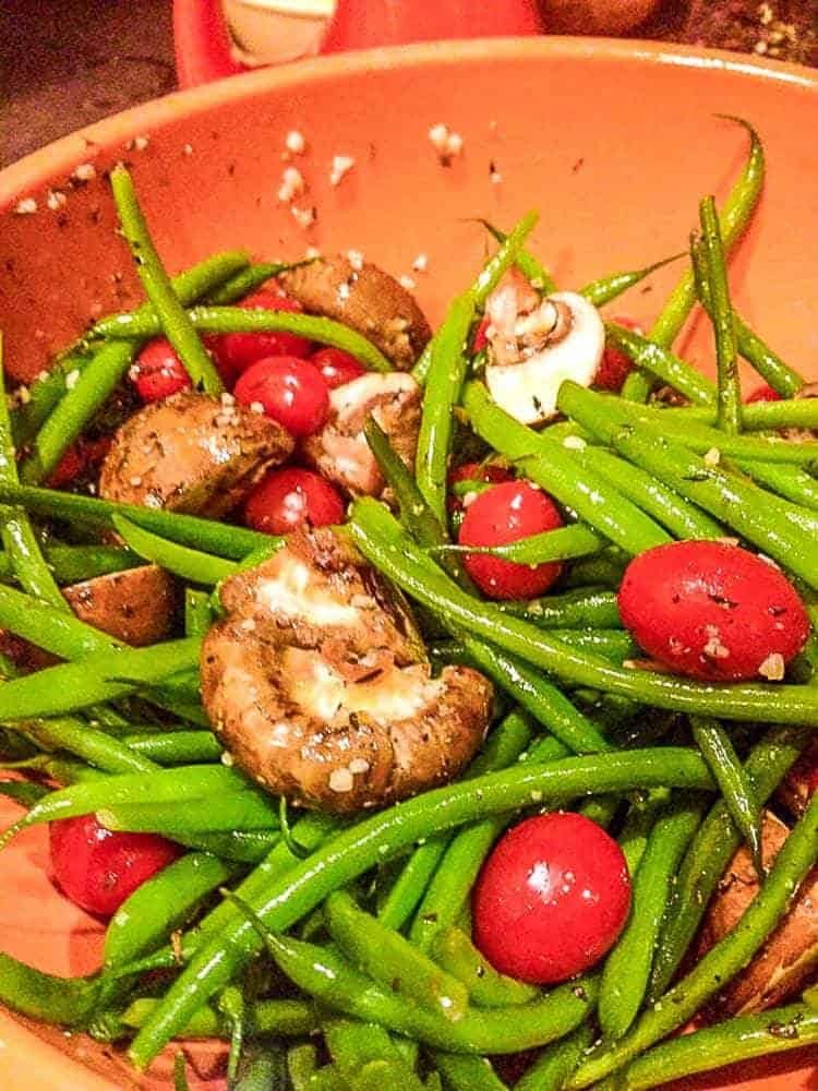 Roasted Green Beans with Tiny Tomatoes and Bleu Cheese  ingredients in a prep bowl tossed with olive oil.