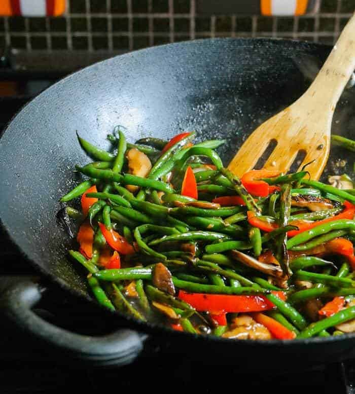 Stir-Fried Green Beans and Shiitake in a wok with a wooden spoon.