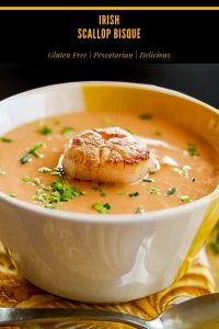 Irish Scallop Bisque with 1 large seared scallop in a yellow and white ceramic bowl.