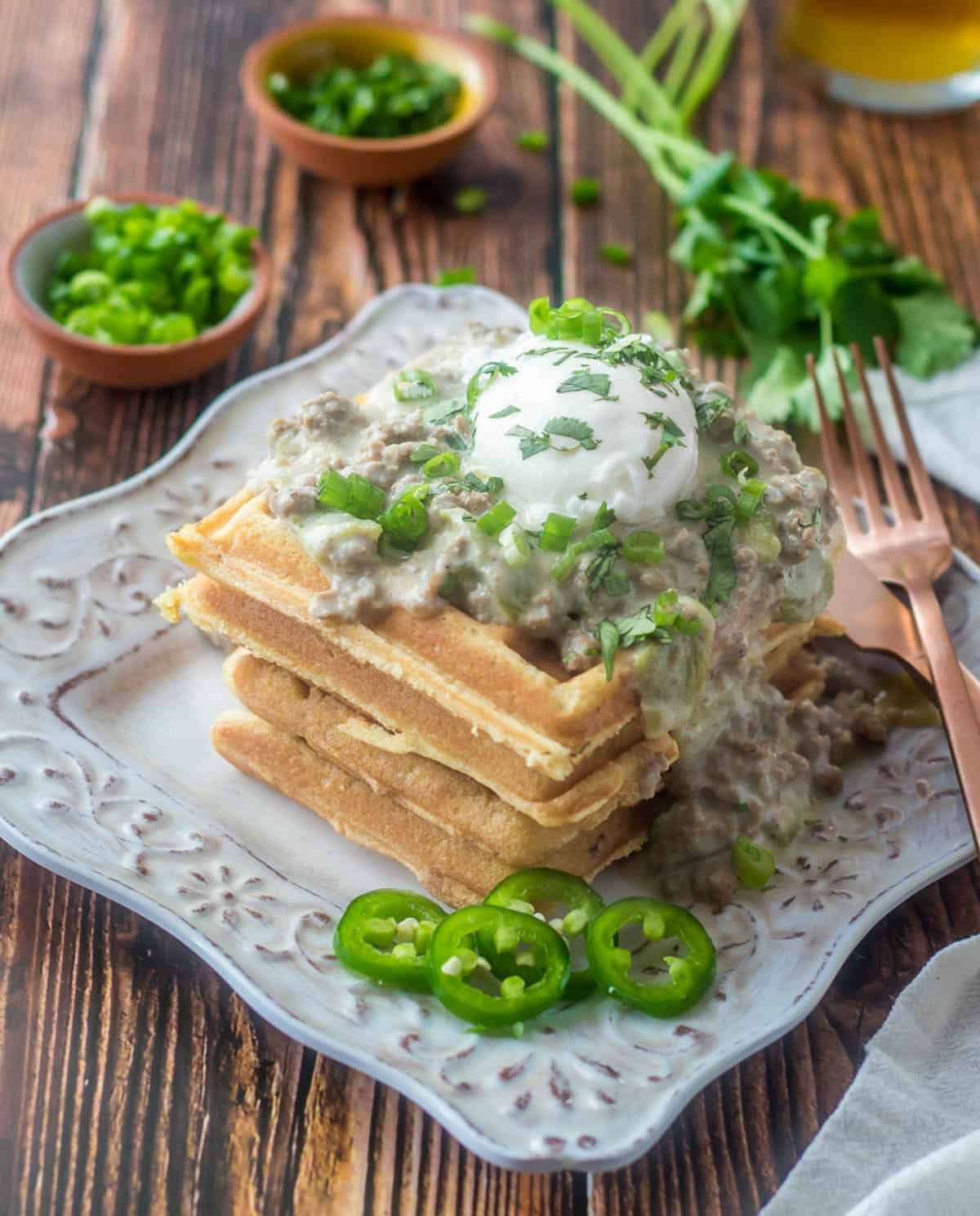 4 cornmeal waffles with Hatch green chile and sausage gravy, a poached egg, and chopped scallion and cilantro.