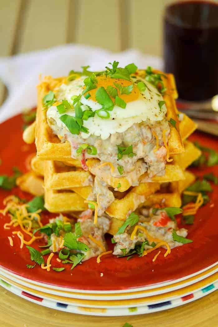 A savory cornmeal waffles stacked high with green chile sausage gravy with an egg on top.