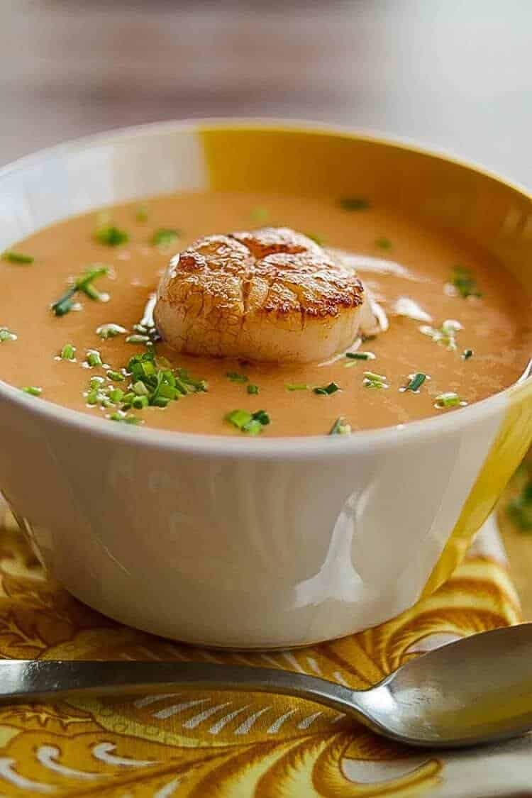 Scallop bisque in a white and yellow bowl with a print napkin.
