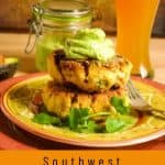 A brightly colored ceramic plate with 2 fish cakes topped with avocado crema with a tall beer behind.