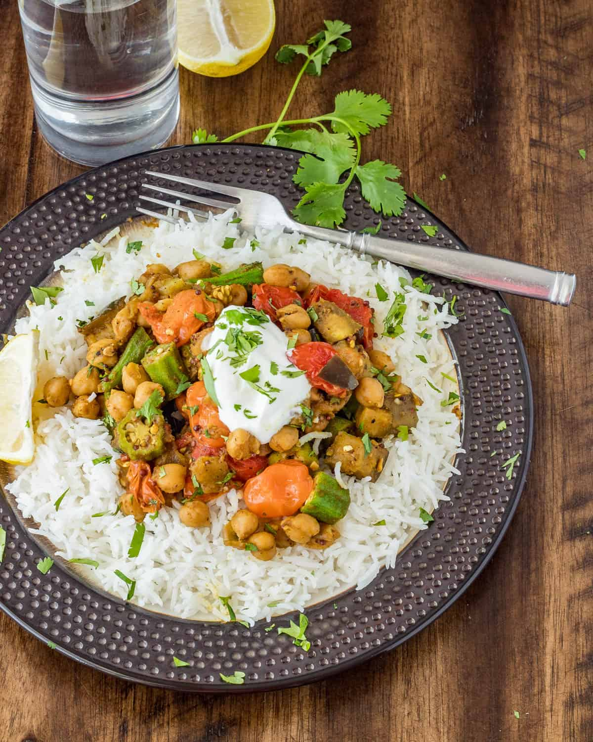 Curried Okra and Eggplant Plated over white rice with a dollop of plain yogurt and garnished with cilantro and lemon wedges.