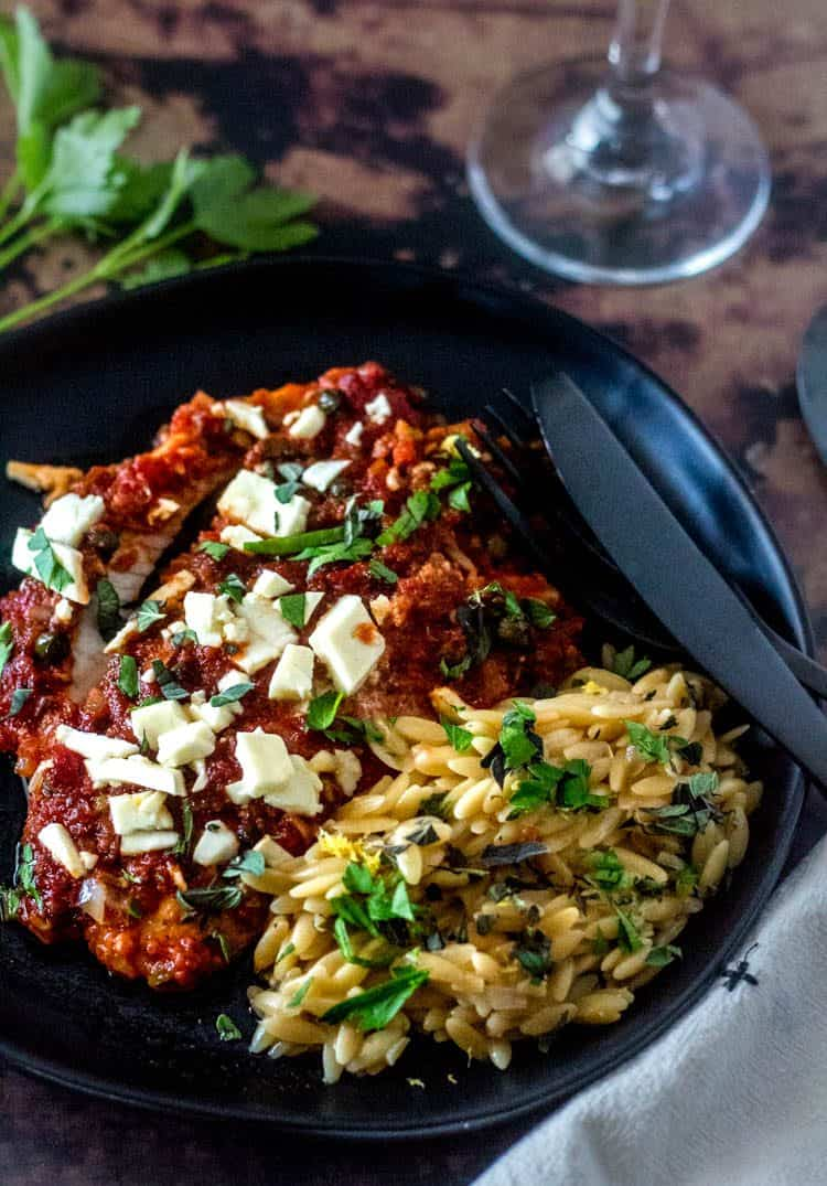 Baked Mediterranean Fish Fillets with Lemony Orzo on a round black ceramic plate with black flatware. It's low calorie, Mediterranean diet compliant, clean, delicious!