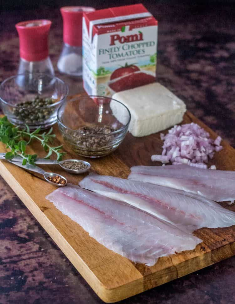 Fish fillets, sauce ingredients, feta set out on a wood cutting board and ready to put together this quick and healthy dish!