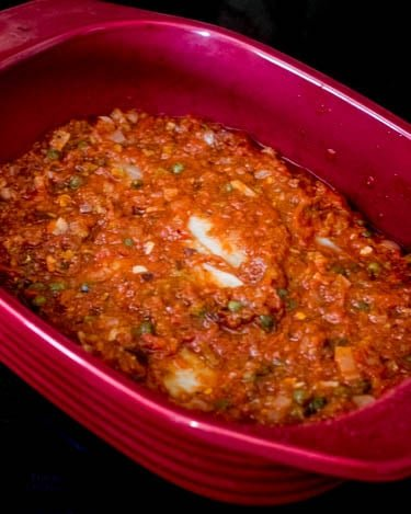 Firm white fish fillets in a red ceramic baking dish with the Mediterranean sauce ready to go in the oven.