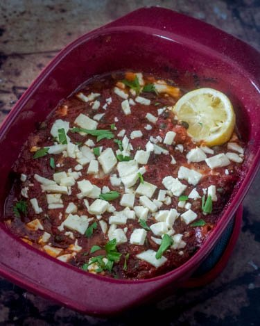 Firm white fish fillets in a red ceramic baking dish with the Mediterranean sauce is baked, topped with feta, parsley, and half a lemon.
