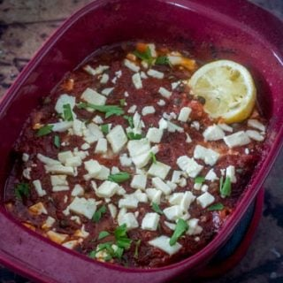 Baked Mediterranean Fish in a red casserole dish is gluten free, clean, healthy, and so delicious!