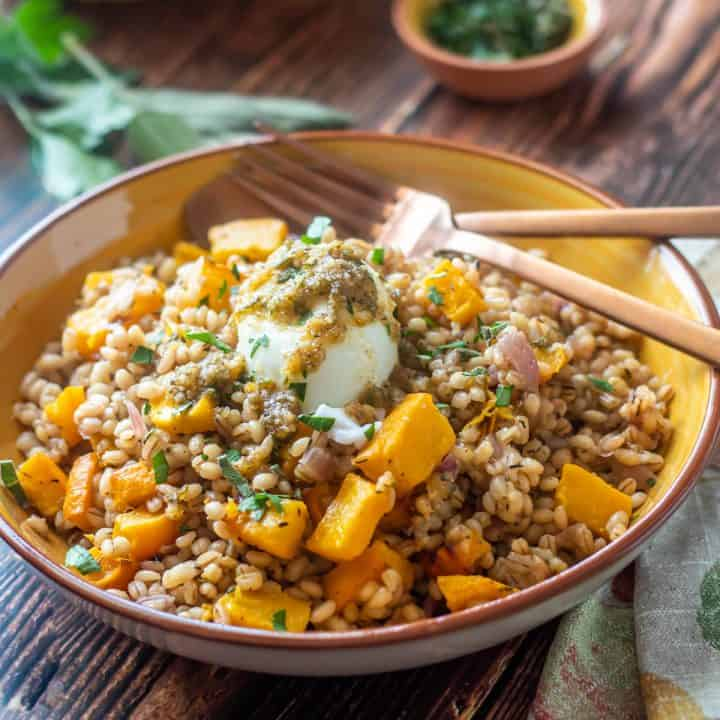 Vegetarian Pumpkin Barley Risotto with a poached egg and sage pesto in a yellow ceramic bowl with copper flatware.