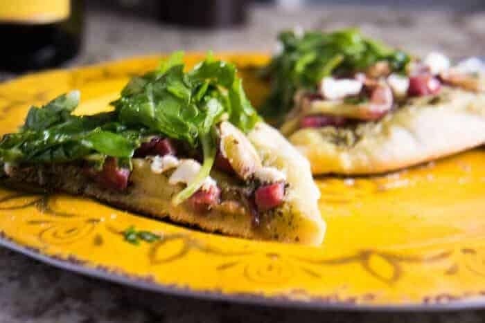 2 slices of pizza topped with arugula salad on a yellow plate.