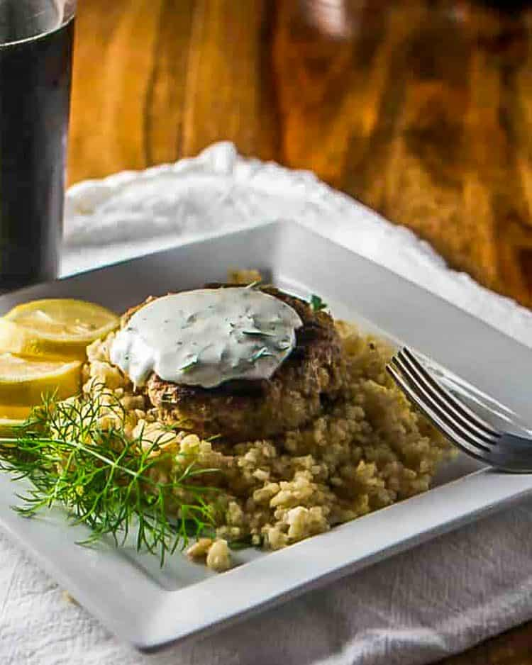 Greek Style Ground Lamb Patties atop bulgar pilaf with a scoop of dill-yogurt sauce, lemon slices on a white plate with dark beer.