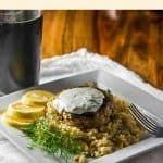 A ground Lamb Patty with bulgar pilaf and yogurt sauce on a white plate