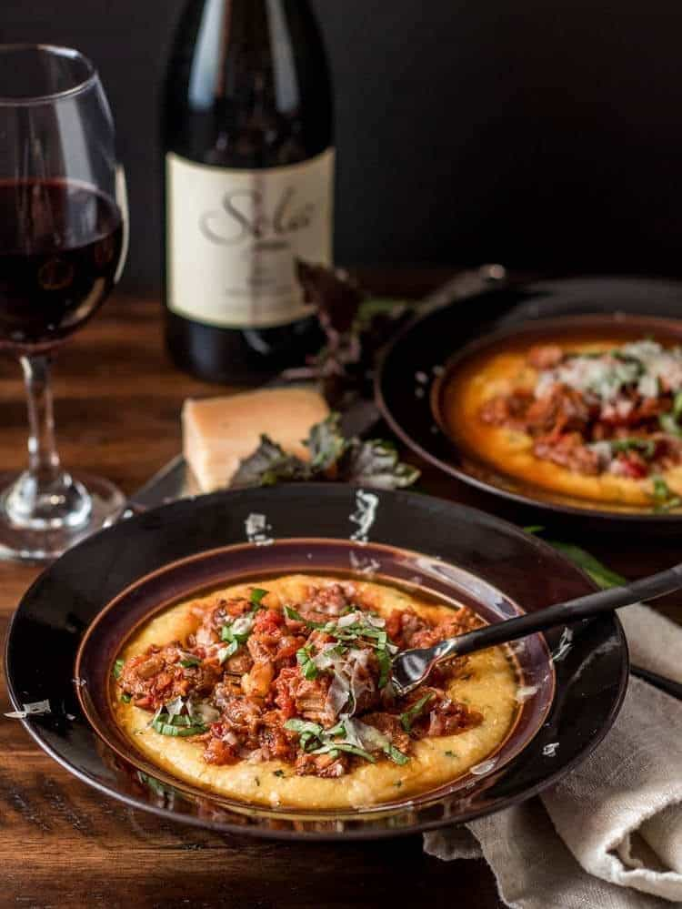 2 brown ceramic bowls with Instant Pot Pork Ragu with Basil Polenta, a linen napkin, and red wine.