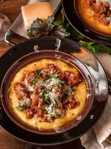 Instant Pot Pork Ragu with Basil Polenta in a brown ceramic bowl with linen napkin.