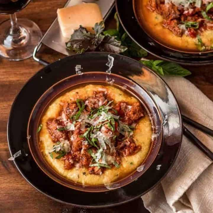 Instant Pot Pork Ragu with Basil Polenta in a brown ceramic bowl with linen napkin.