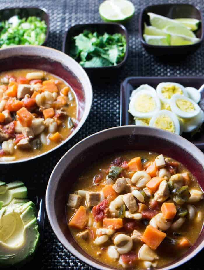Peruvian Chicken and Corn Stew  in 2 bowls before toppings - hard cooked egg, cilantro, lime, avocado - are added.