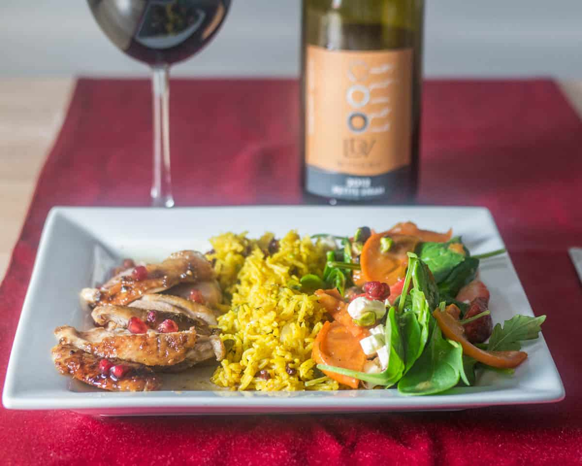 Za'atar and Pomegranate Molasses Roasted Duck  sliced on a plate with pistachio rice and a persimmon and strawberry salad on a white plate.