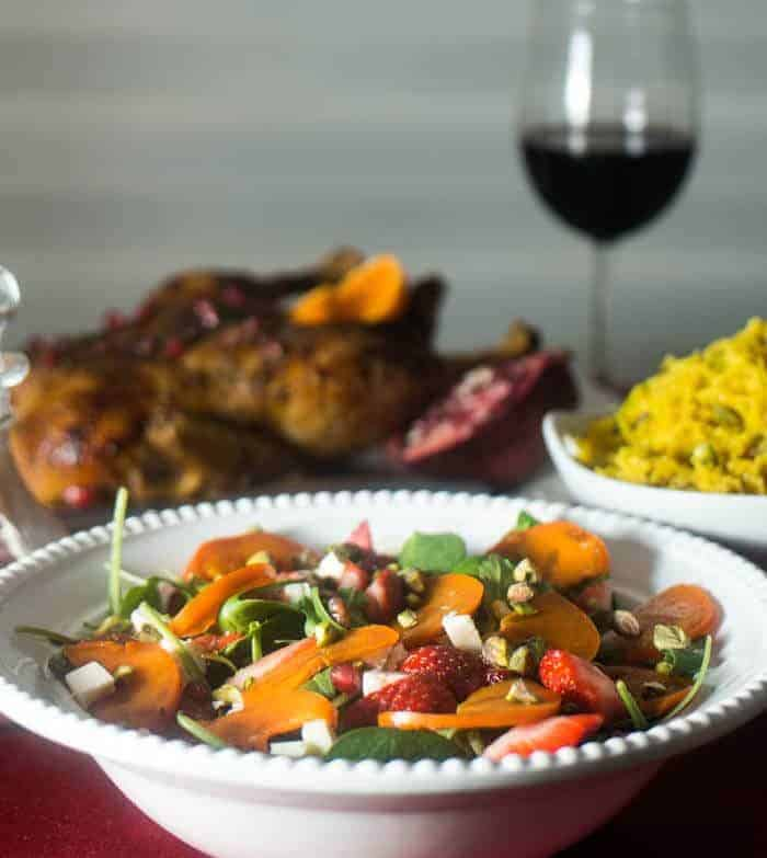 Spinach and Persimmon Salad with Za'atar Roasted Duck and Pistachio Pilaf on a white square plate with a glass of red wine.