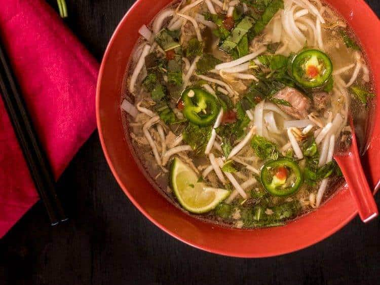 Instant Pot Beef Pho in a deep bowl with a red napkin and fresh basil sprig.
