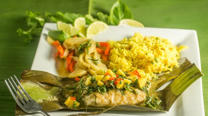 A close up of Thai Curried Snapper In Banana Leaves on a white plate.