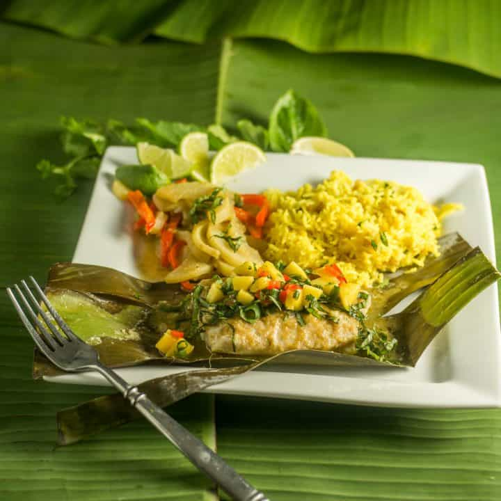 A stack of banana leaves, with a white plate of Thai fish in banana leaves with mango salsa.