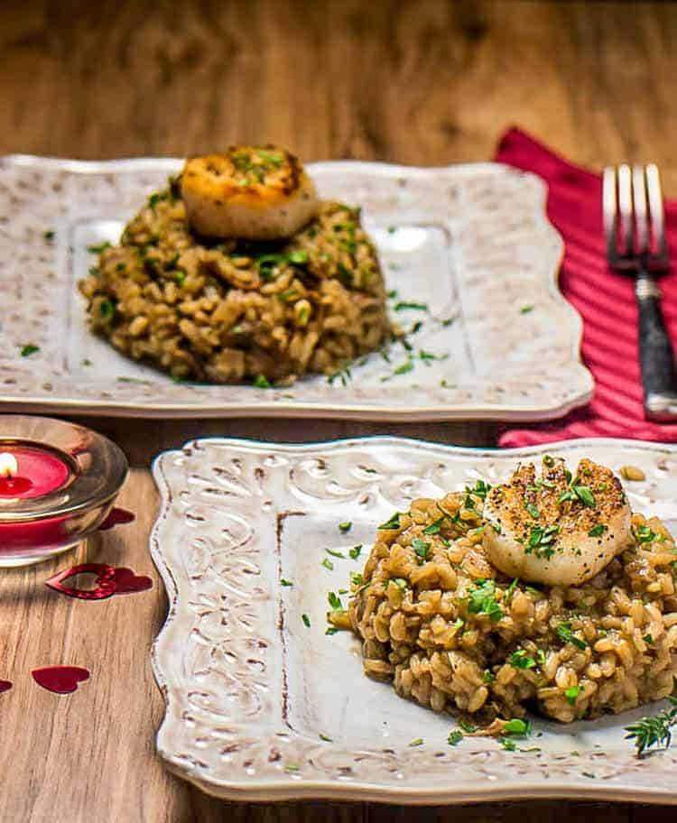 Seared Scallop with Mushroom Risotto - two servings on beige plates, red napkin, candle...