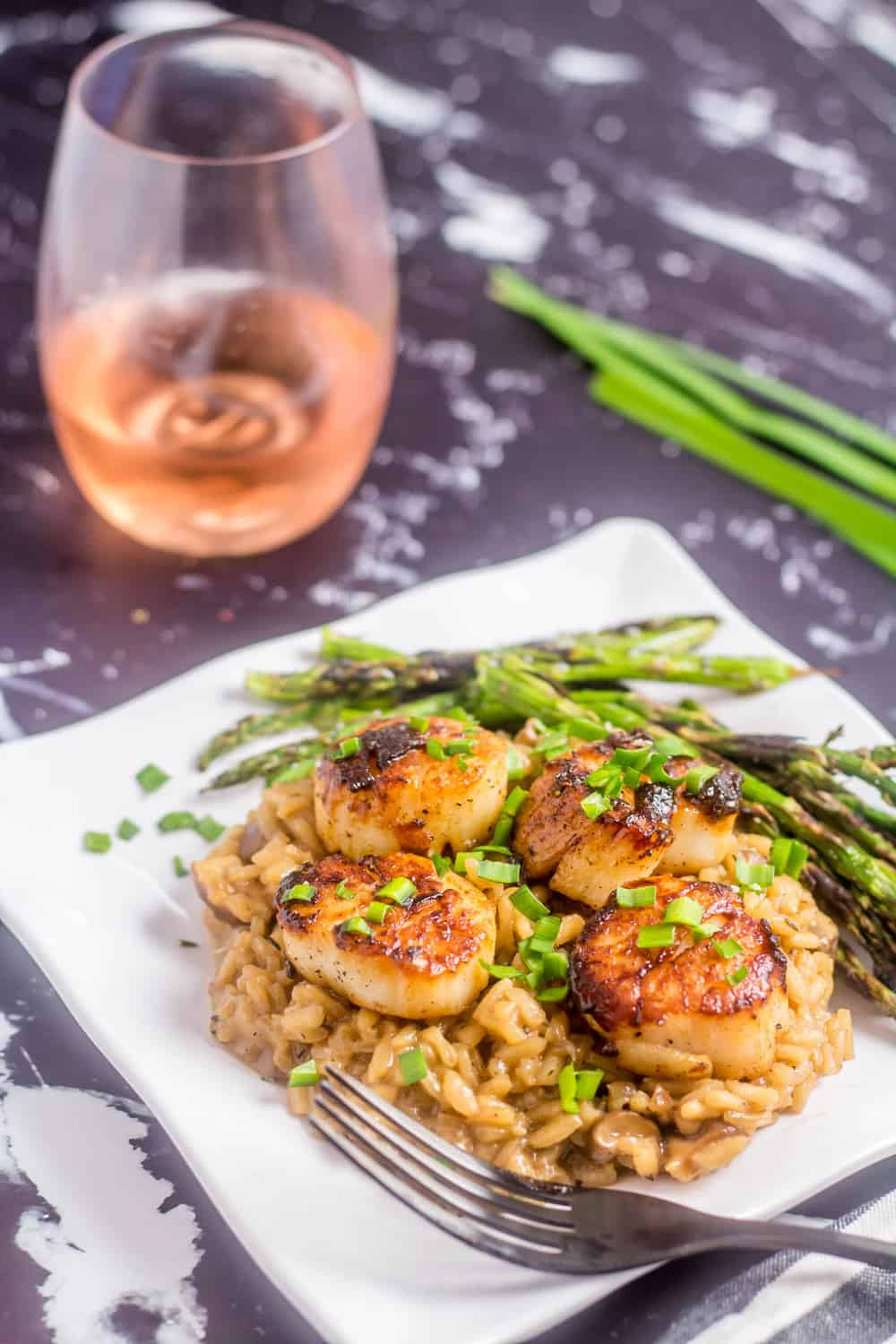 A square white plate with gluten free mushroom risotto topped with 4 perfectly seared scallops, paired with grilled asparagus and a glass of dry rosé
