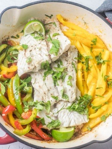 Caribbean Style Fish With Orange Ginger Salad on a white ceramic plate with orange salad and coconut rice in the background.