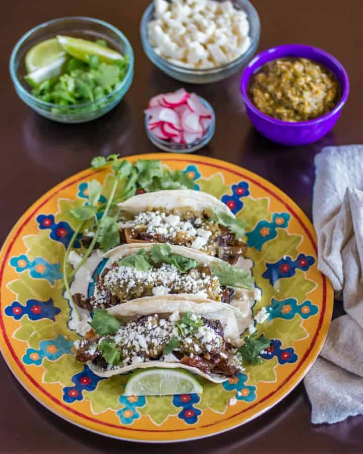 A plate of tacos with all the toppings - cilantro, lime, cotija, salsa verde, radishes.